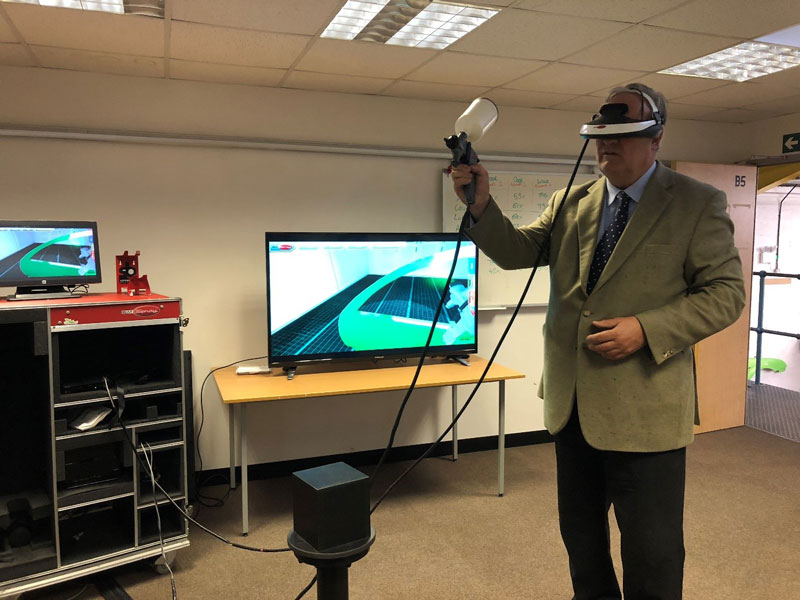 James Gray MP trying out the virtual reality auto-paint spraying machine